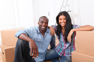 Cheerful couple sitting in empty new house